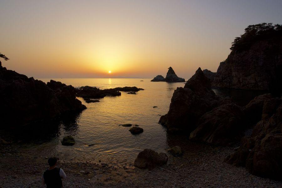 日本海の水平線に沈む夕日を眺める